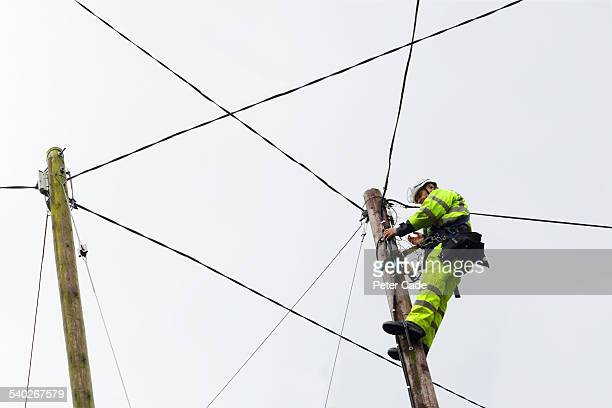 Engineer fixing wires, high up in air .