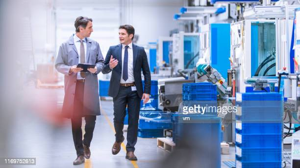 ingenieur gibt manager eine führung durch eine fabrik - herstellendes gewerbe stock-fotos und bilder