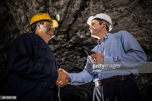 Engineer greeting a miner with a handshake