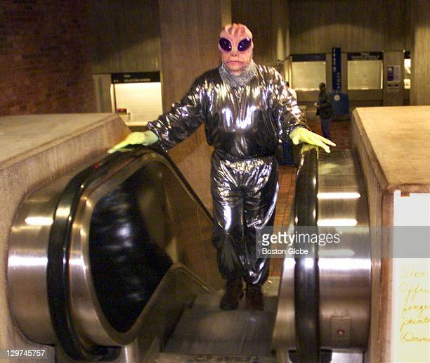 Engineer Harry Tripp dressed in an alien costume rides the escalator to the third floor of Boston City Hall to entertain kids at the Haunted...