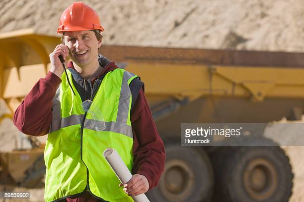 Engineer holding a blueprint and talking on a walkie-talkie