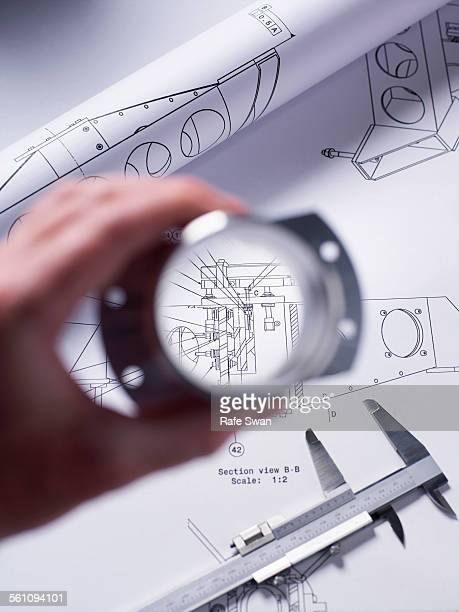 Engineer holding a precision made component over a technical drawing with a dial caliper