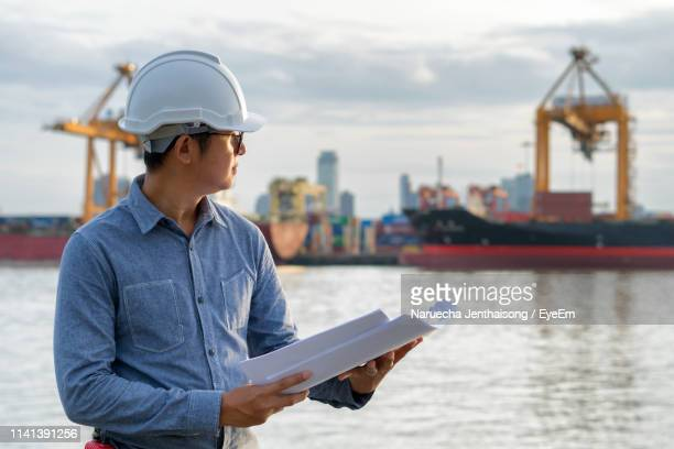 engineer holding blueprint while standing by sea against shipping industry - marine engineering stock pictures, royalty-free photos & images