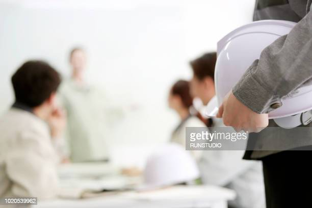 engineer holding hard hat in meeting - risques liés à une activité photos et images de collection