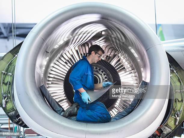Engineer holding jet engine turbine blade in aircraft maintenance factory
