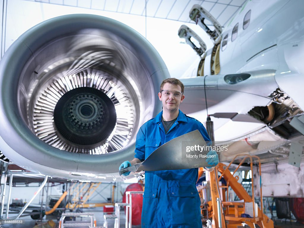 engineer holding jet engine turbine blade in aircraft maintenance factory portrait stock photo