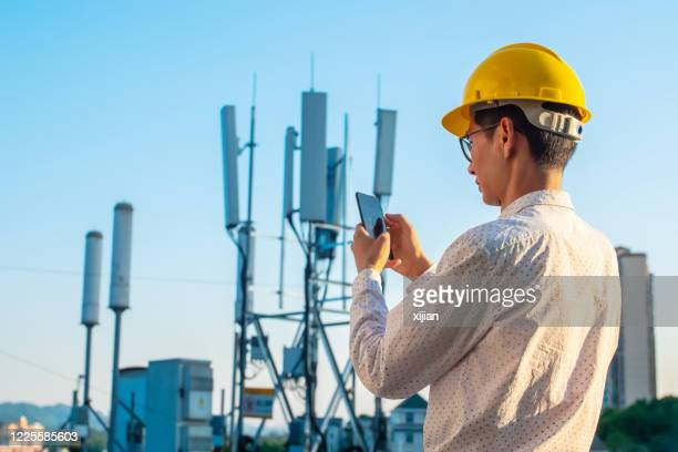 engineer holding mobile phone testing the communications tower - bandwidth stock pictures, royalty-free photos & images