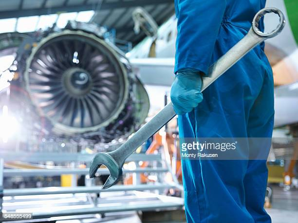 Engineer holding spanner in aircraft maintenance factory, close up