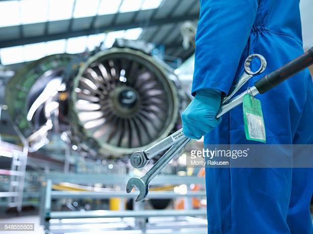 Engineer holding tools in aircraft maintenance factory, close up