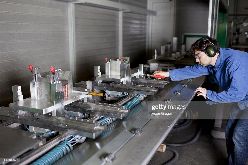 Engineer Improving The Setup Of A Big Machine Stock Photo