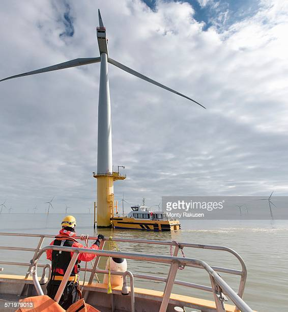 engineer in boat at offshore windfarm turbine - marine engineering stock pictures, royalty-free photos & images