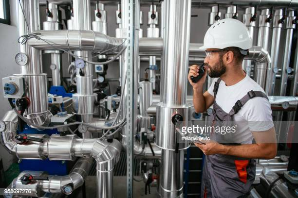 Engineer in boiling room with tablet and walkie-talkie