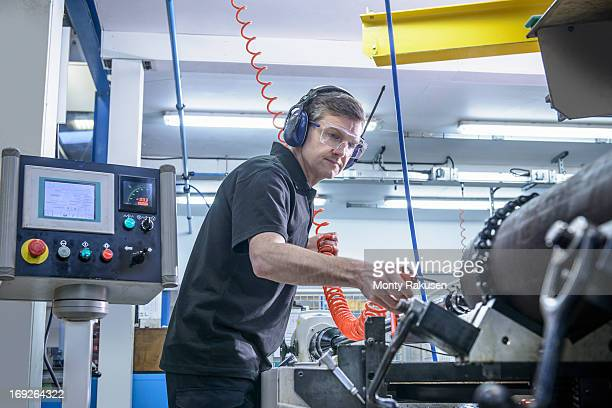 Engineer in ear defenders and safety glasses cleaning steel bar on lathe