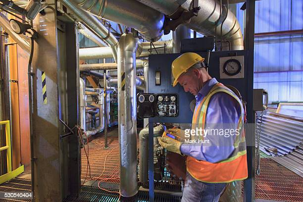 Engineer in electric power plant using a voltmeter to verify sensor readings