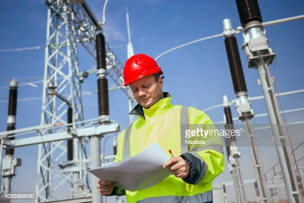 engineer in electricity station looking at blueprint - power line stock photos and pictures
