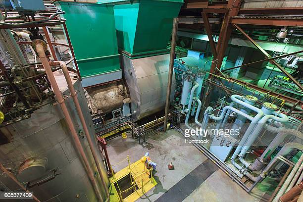 Engineer in gas turbine electric power plant exhaust gas and condensation process room looking at coolant water pit