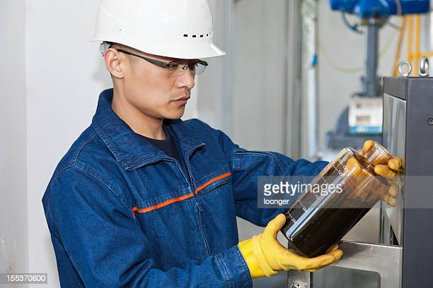 Engineer in hard hat examining an oil sample