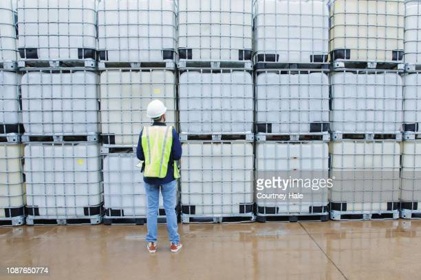 engineer in oil and gas industry checks inventory of chemical crates. - storage tank stock pictures, royalty-free photos & images