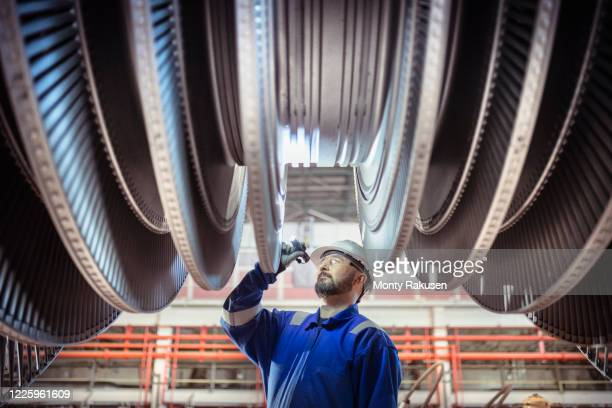 engineer inspecting a turbine in a  nuclear power station. - atomic imagery stock pictures, royalty-free photos & images