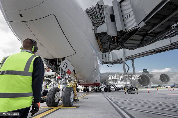 Engineer inspecting A380 aircraft at stand in airport