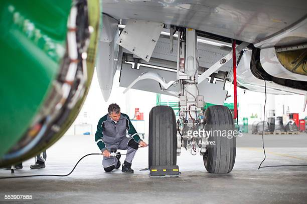 Engineer inspecting aircraft tires in hangar
