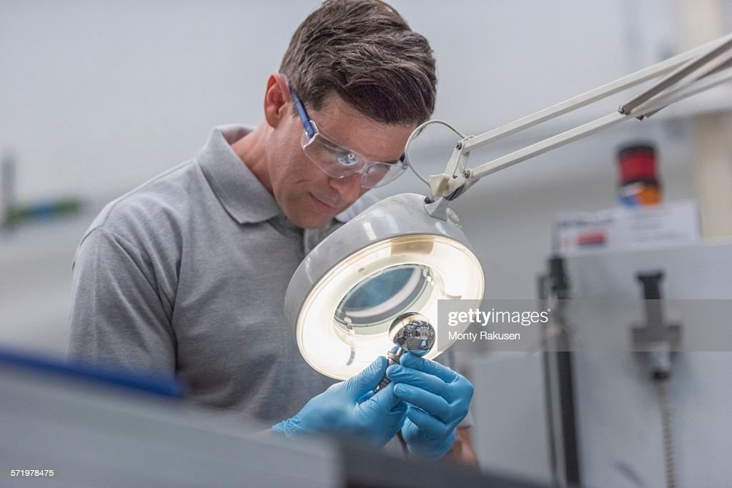 Engineer inspecting artificial hip joint in orthopaedic factory : Stock Photo