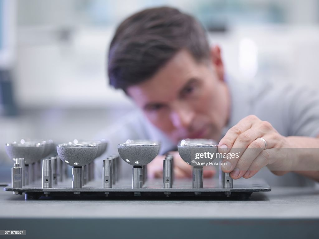 Engineer inspecting artificial hip joint parts in quality control department in orthopaedic factory : Stock Photo