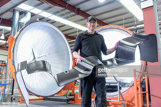 Engineer inspecting carbon fibre body part in front of autoclave in racing car factory