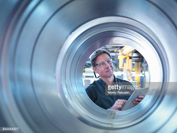 engineer inspecting finished parts in factory - metallic look stock pictures, royalty-free photos & images