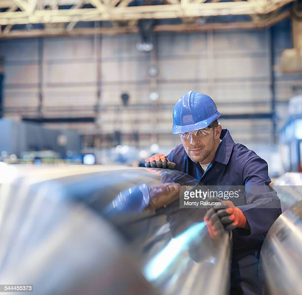 Engineer inspecting finished steel roller in engineering factory