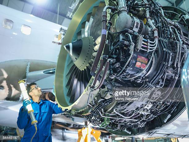engineer inspecting jet engine in aircraft maintenance factory - jet engine stock photos and pictures