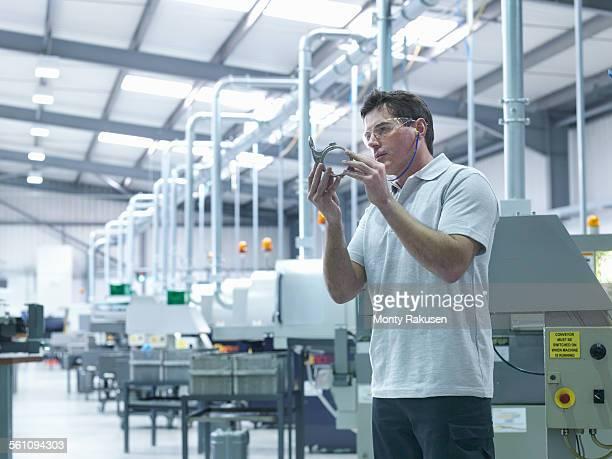 engineer inspecting part on production line - monty rakusen stock-fotos und bilder