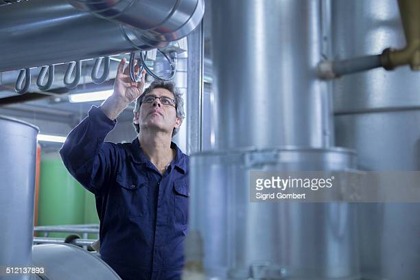 Engineer inspecting pipes in power station