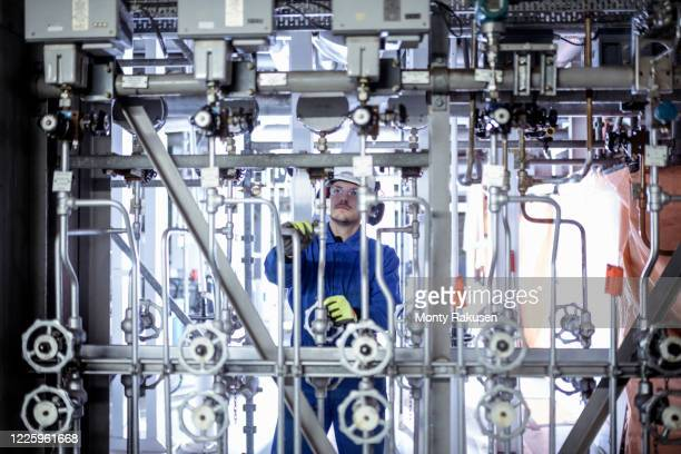 engineer inspecting pipework in a nuclear power station. - atomic imagery stock pictures, royalty-free photos & images