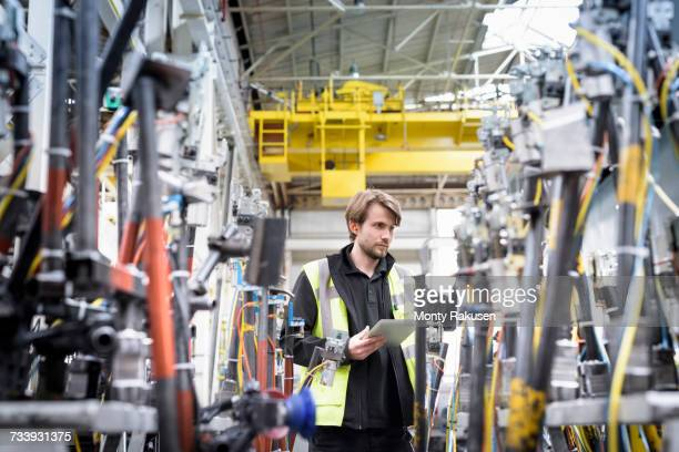 Engineer inspecting press machinery in car factory
