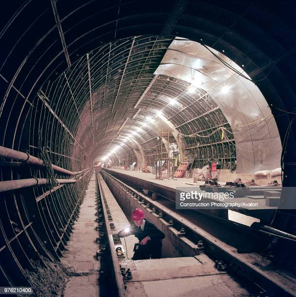 Engineer inspecting rail installation in the new tunnel and platform area of Angel Station London United Kingdom 27th November 2002