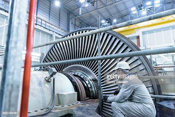 engineer inspecting steam turbine in gas-fired power station - monty rakusen stock-fotos und bilder