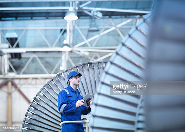 Engineer inspecting steam turbine in repair bay