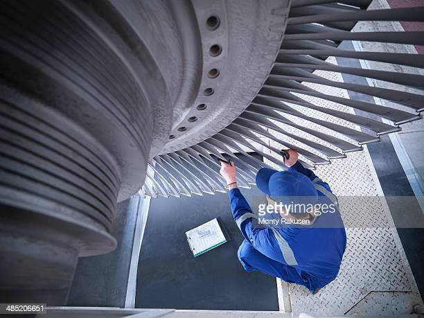 Engineer inspecting steam turbine in repair works