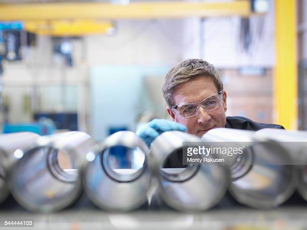 Engineer inspecting steel parts in factory