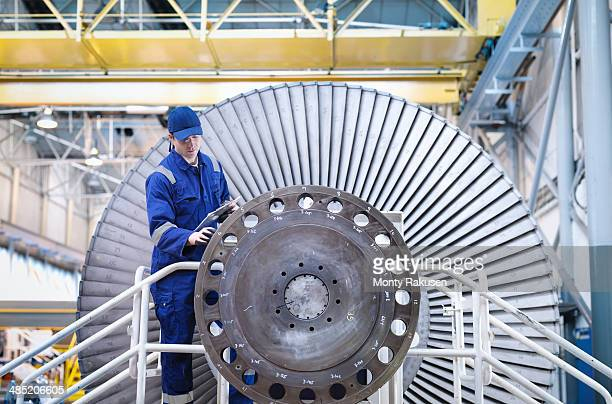 Engineer inspecting turbine in workshop