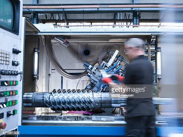 Engineer inspecting worm drive gear in lathe in engineering factory