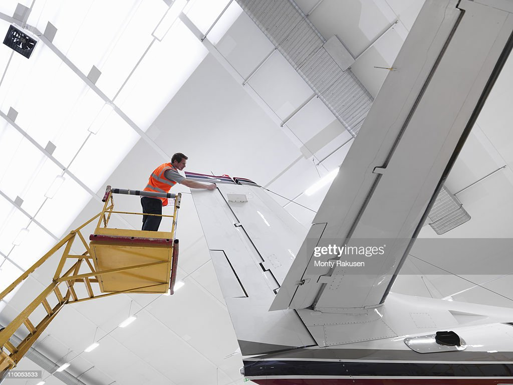 Engineer inspects jet aircraft : Stock Photo