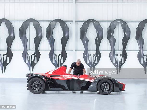 Engineer inspects supercar in factory with carbon fibre car body shells hanging on wall