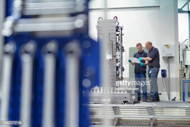 Engineer instructing apprentice on CNC machine in gearbox factory
