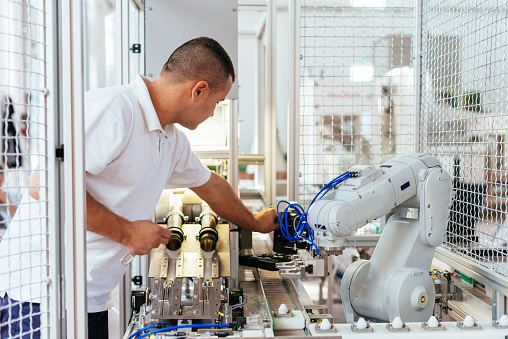 Engineer is examining modern production line robot - gettyimageskorea