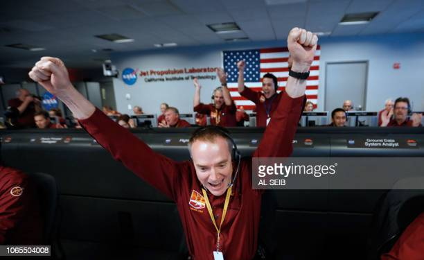 TOPSHOT NASA engineer Kris Bruvold reacts after the successfull landing by the InSight spacecraft on the planet Mars from the Mission Support area in...