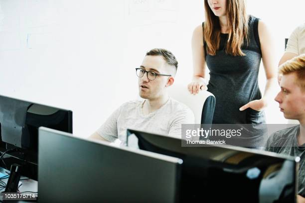 engineer leading discussion with coworkers while solving coding problem - digital native stock pictures, royalty-free photos & images