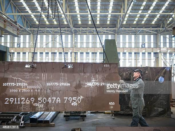 Engineer lifting steel plate in factory