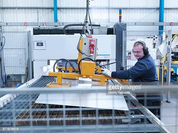 engineer loading sheet metal into laser cutter in engineering factory - monty rakusen stock-fotos und bilder